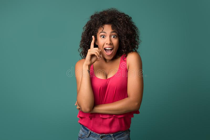 African-american girl having idea against blue background stock image