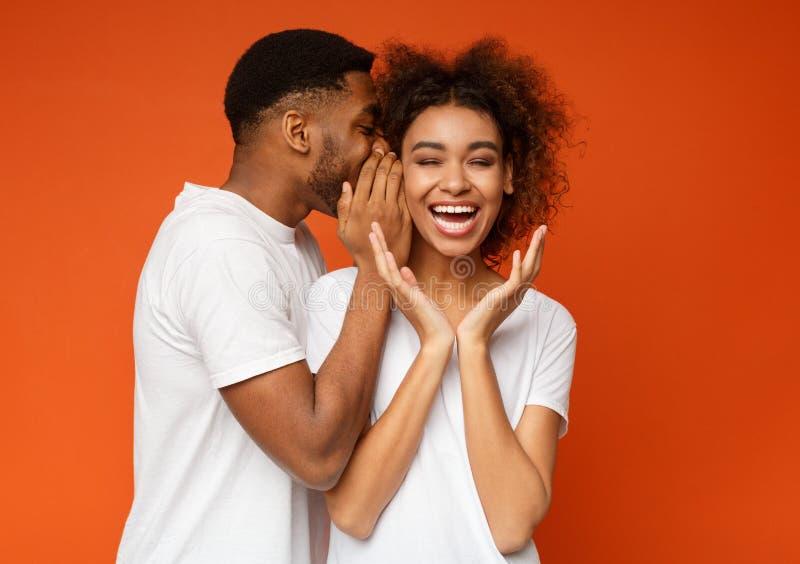 Black man sharing secret with his girlfriend. African-american girl laughing, listening how her boyfriend whispering secret or gossips, orange studio background royalty free stock photos