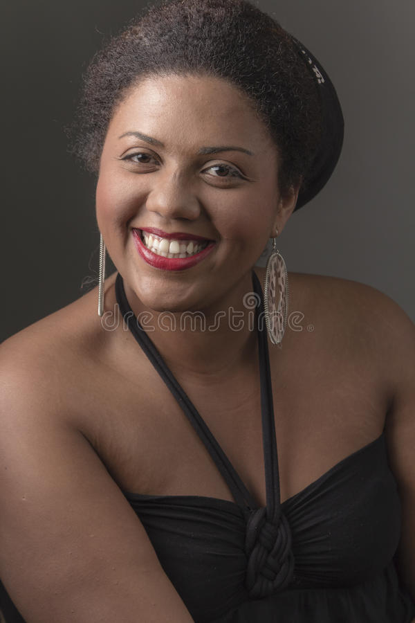African american girl laughing sincerely. Young female, big eyed beauty, smiling cordiallynYellow/gray background royalty free stock photo