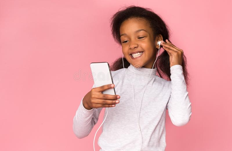 African-american girl listening music on smartphone over background royalty free stock photo