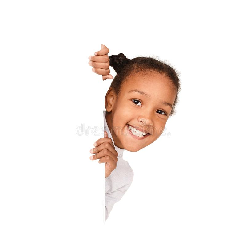 African-american girl peeking out from empty banner. Isolated on white background royalty free stock photos