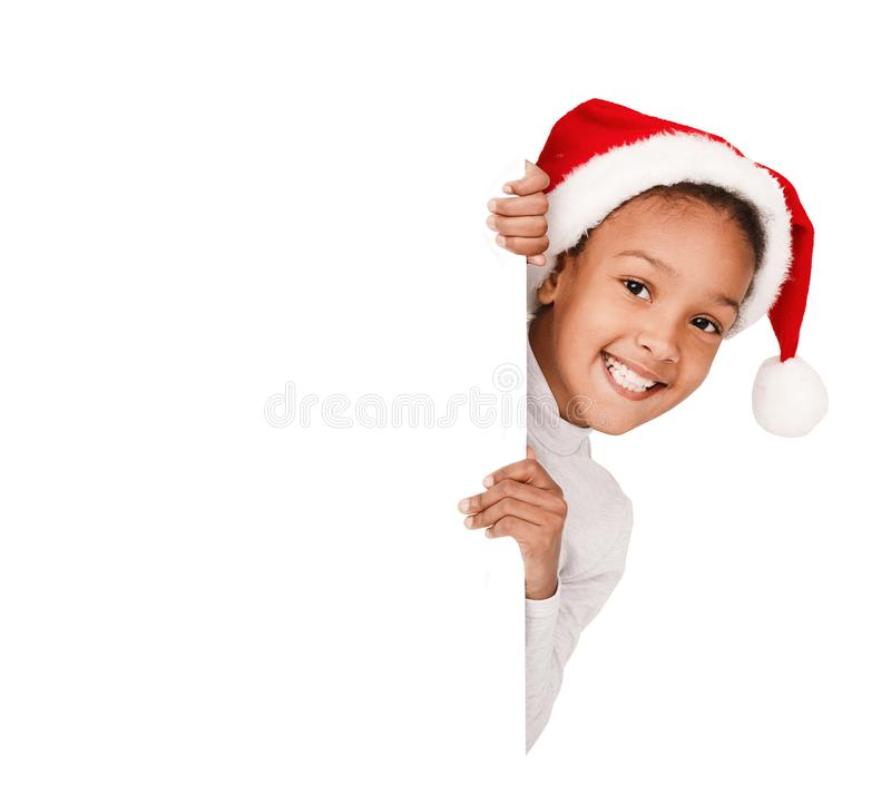 African-american girl peeking over blank board, wearing santa hat. Isolated on white background royalty free stock image