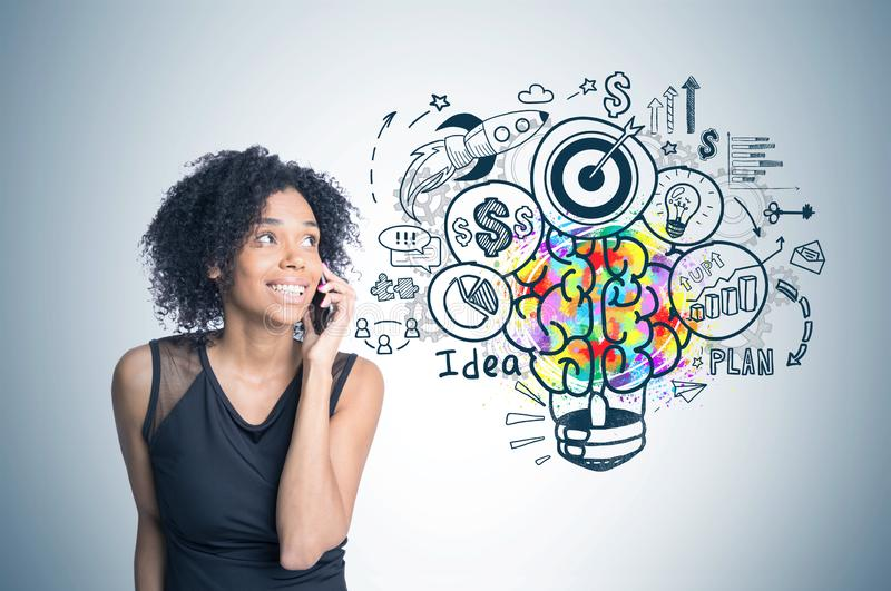 African american girl on phone, business idea. Smiling african american woman talking on phone standing near gray wall with colorful business idea sketch drawn royalty free stock image