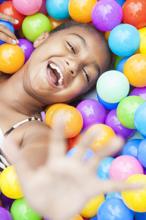 African American Girl Playing in Colored Balls royalty free stock image