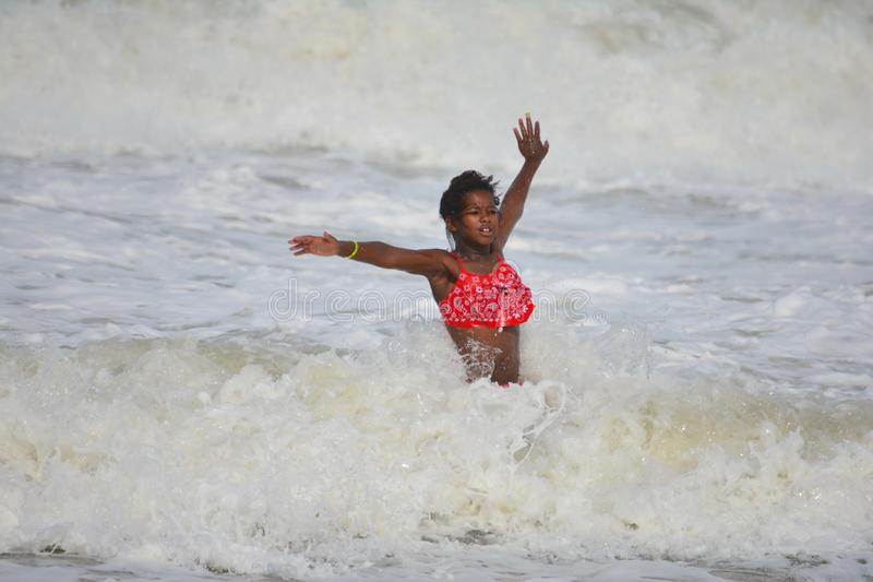 African American Girl Playing in Ocean Waves royalty free stock photo