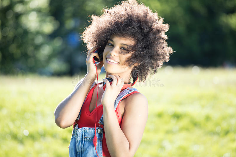 African american girl relaxing outdoor with headphones. Photo of young african american girl with headphones, smiling. Outdoor photo royalty free stock image