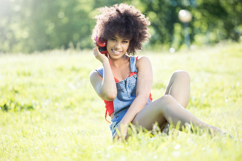 African american girl relaxing outdoor with headphones. Photo of young african american girl with headphones, smiling, sitting on the grass. Outdoor photo royalty free stock image