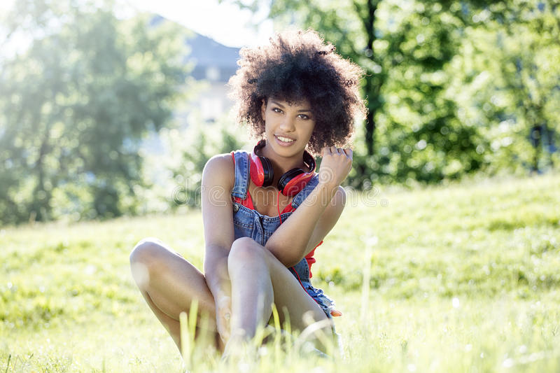 African american girl relaxing outdoor with headphones. Photo of young african american girl with headphones, smiling, sitting on the grass. Outdoor photo royalty free stock photography