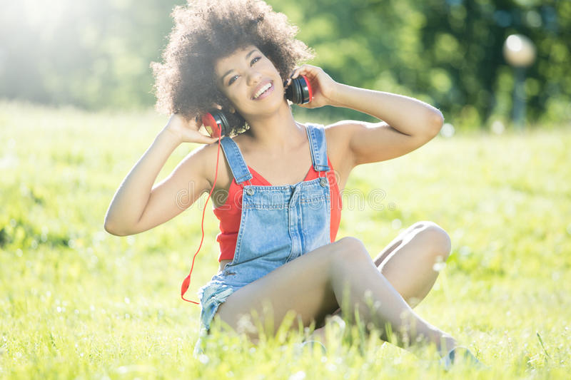 African american girl relaxing outdoor with headphones. Photo of young african american girl with headphones, smiling, sitting on the grass. Outdoor photo royalty free stock images
