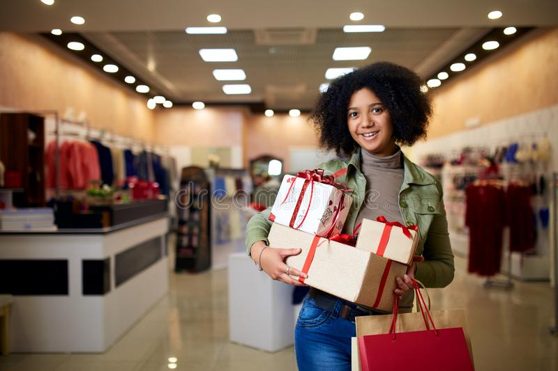 African american girl shopping gifts in mall on christmas sale. New year holidays concept. Smiling attractive mixed royalty free stock photo