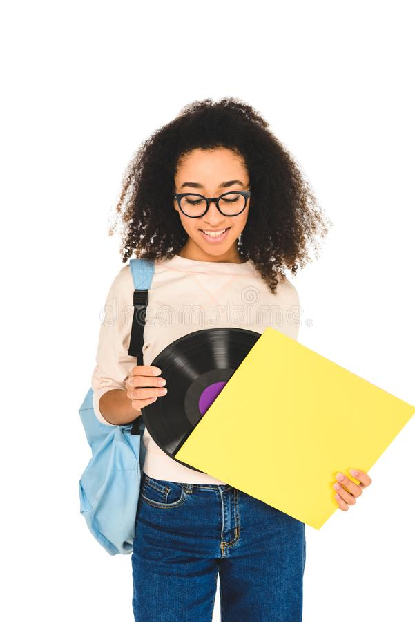 African american girl standing in glasses and looking at vinyl record isolated. On white royalty free stock photos