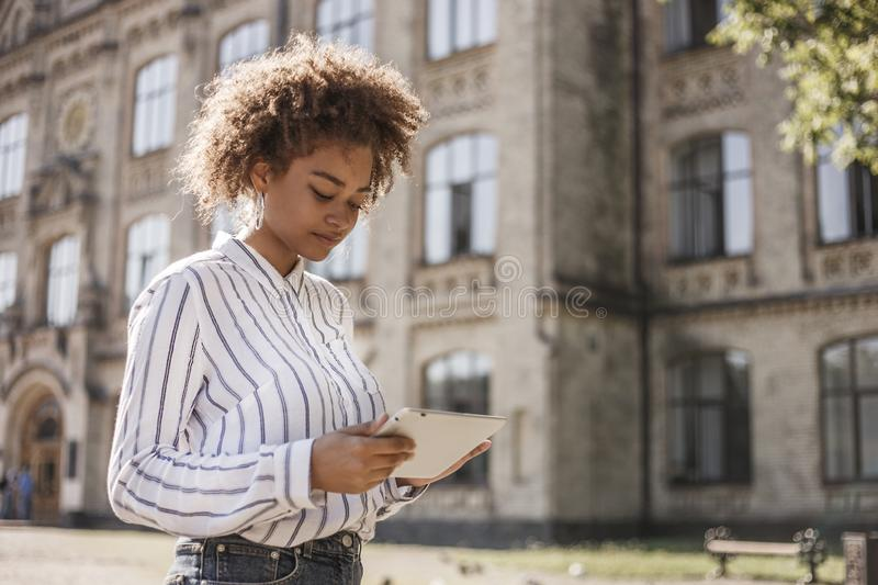 African-American girl standing on the street near the University. She holds the tablet in her hands and looks at it.  royalty free stock photography