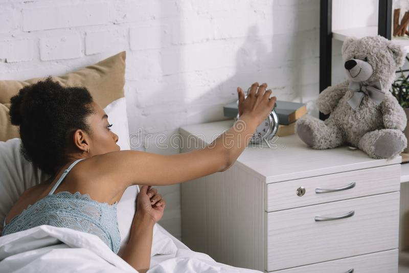 African american girl waking up and turning off alarm clock. In bedroom royalty free stock photography