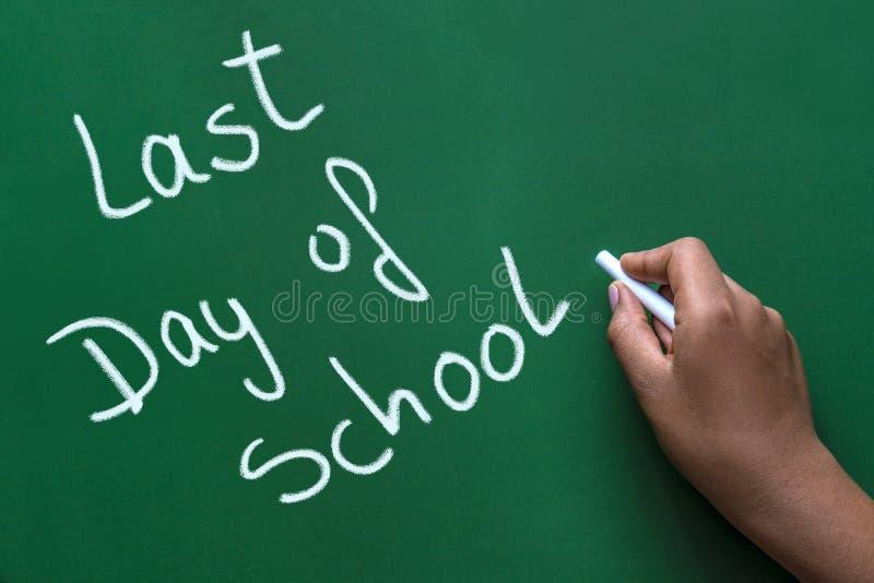Last day of school written in white chalk on a green chalkboard stock images