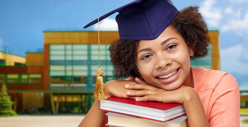 African american graduate student with books. Education, graduation and knowledge concept - happy smiling african american graduate student girl in bachelor cap royalty free stock image