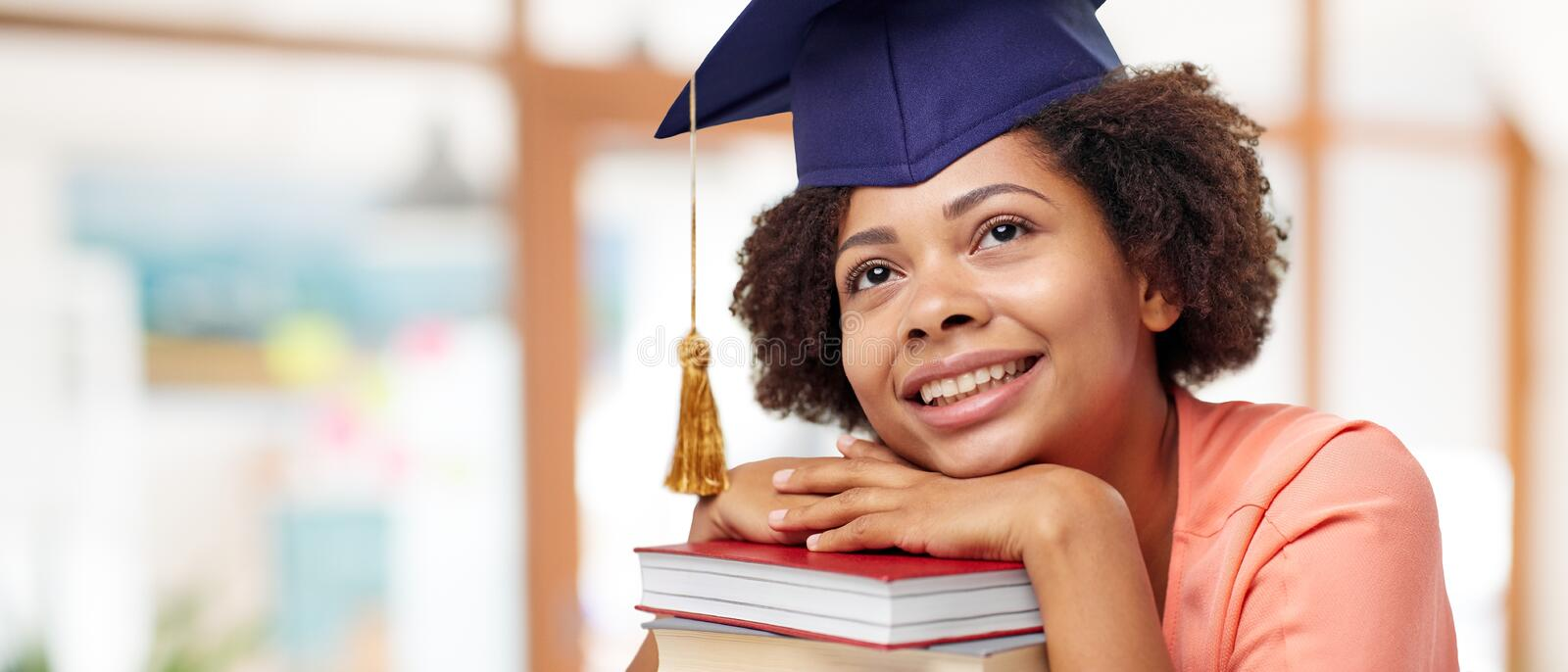 African american graduate student with books. Education, graduation and knowledge concept - happy smiling african american graduate student girl in bachelor cap royalty free stock photography