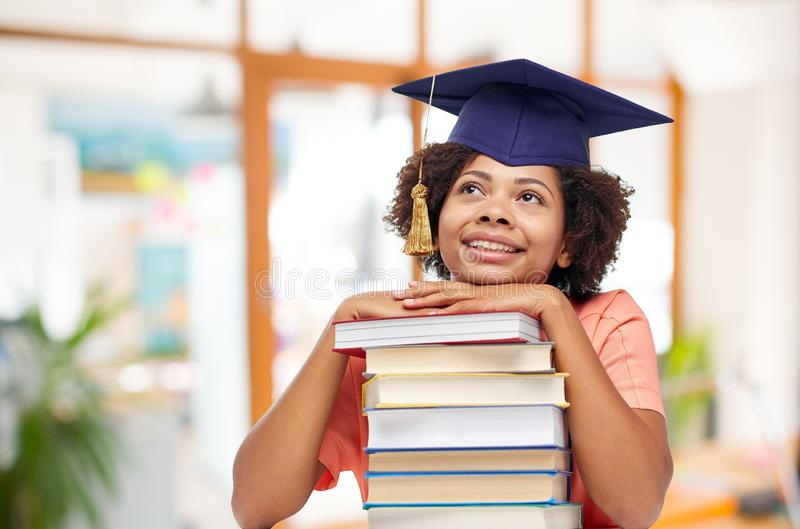 African american graduate student with books. Education, graduation and knowledge concept - happy smiling african american graduate student girl in bachelor cap stock image