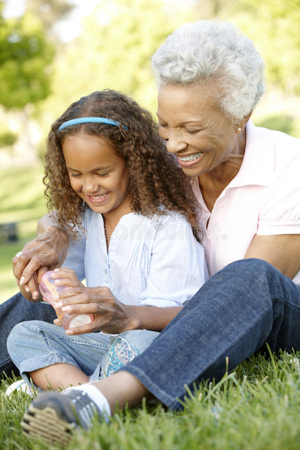 African American Grandmother And Granddaughter Blowing Bubbles I royalty free stock photography