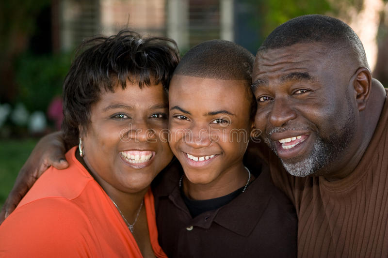 African American grandparents and their grandson. Portrait of an African American grandparents hugging their grandson stock image