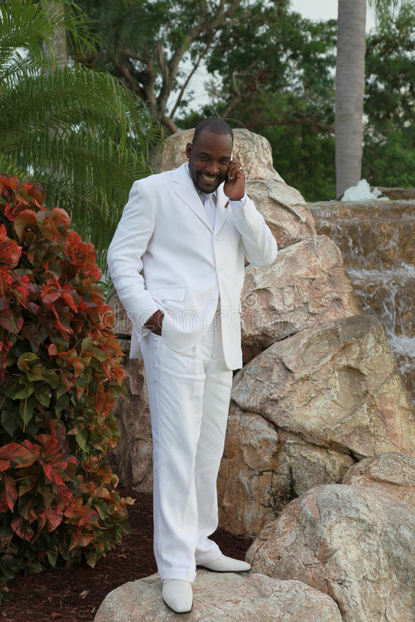 African American Groom. A handsome African american man standing in a tropical setting wearing a white tuxedo talking on a cell phone royalty free stock photos