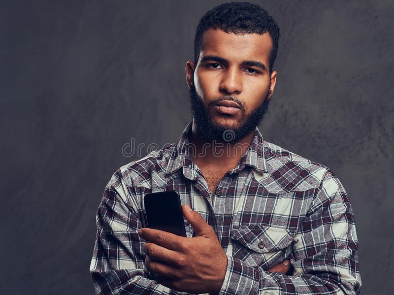 African-American guy with a beard wearing a checkered shirt holding a phone in a studio. Portrait of African-American guy with a beard wearing a checkered shirt stock images
