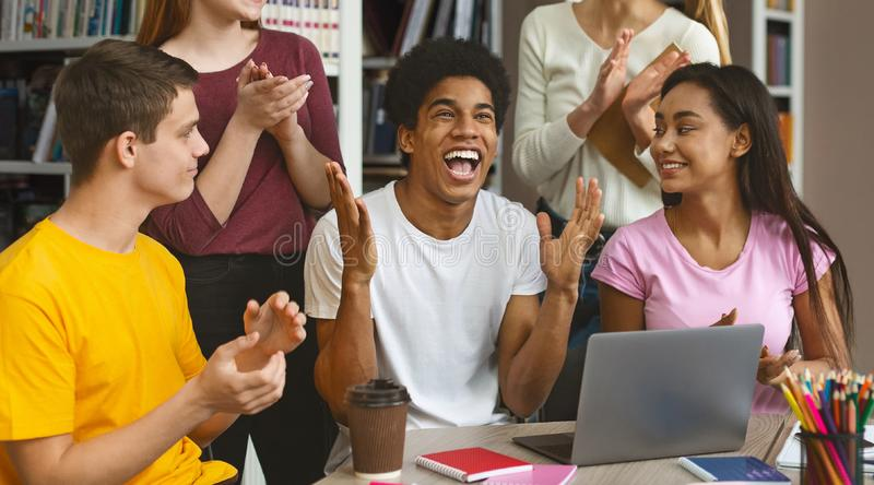 African american guy celebrating high exam results. Joy of success. Emotional afro guy expressing happines, his friends supposrting him, library interior royalty free stock image