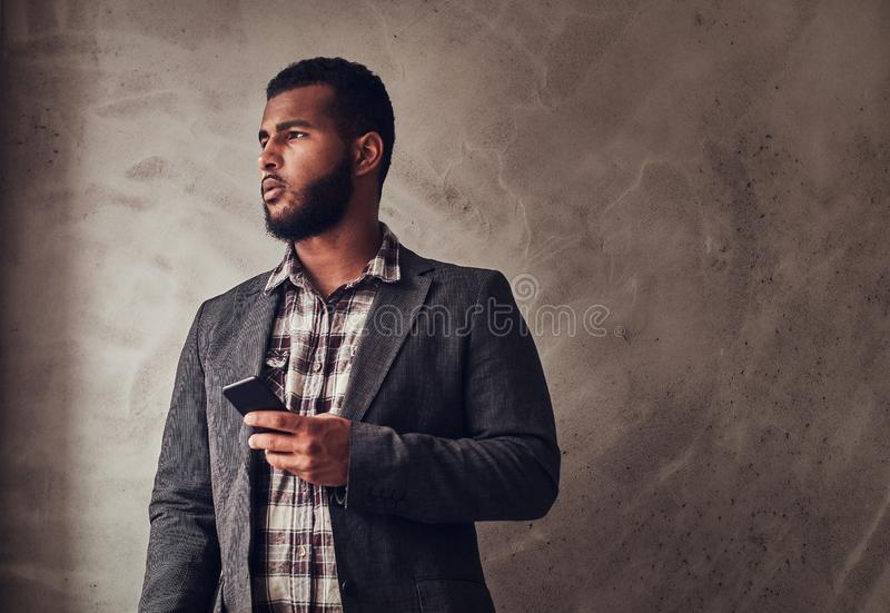 African-American guy holding a phone in a studio. African-American guy holding a phone while standing next to a textured gray wall in a studio royalty free stock image