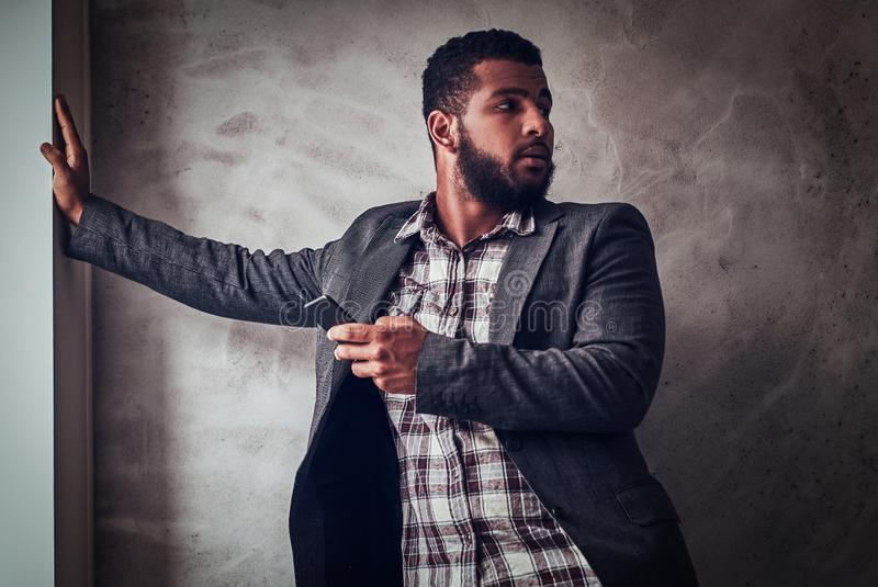 African-American guy holding a phone and turning around in a studio. African-American guy holding a phone and turning around while standing next to a textured royalty free stock images