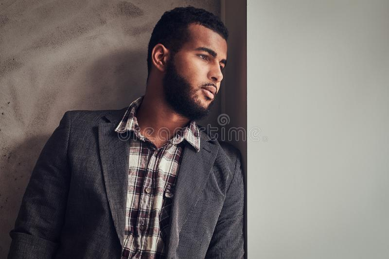 African-American guy leaning on a wall and looking away. African-American guy wearing a jacket and checkered shirt leaning on a wall and looking away royalty free stock photo