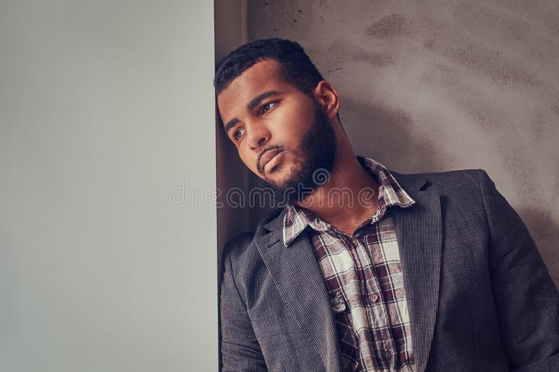 African-American guy leaning on a wall and looking away. African-American guy wearing a jacket and checkered shirt leaning on a wall and looking away stock images