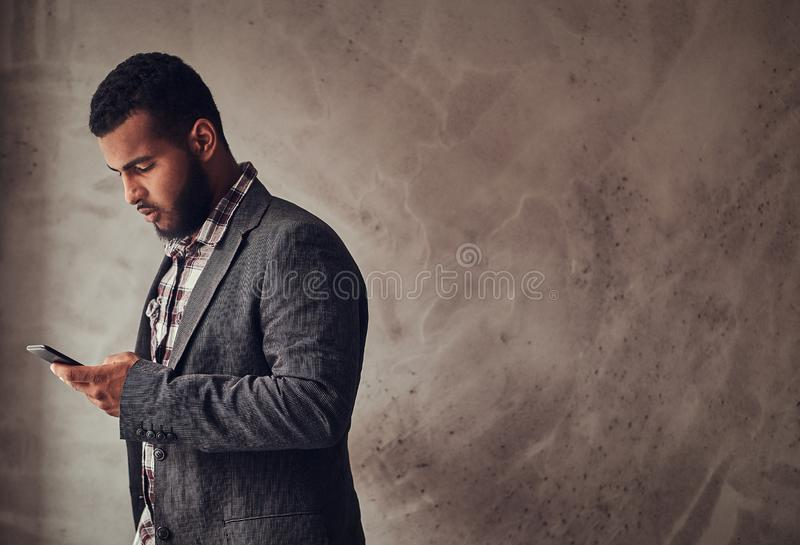 African-American guy using a phone in a studio. African-American guy using a phone while standing next to a textured gray wall in a studio royalty free stock photography