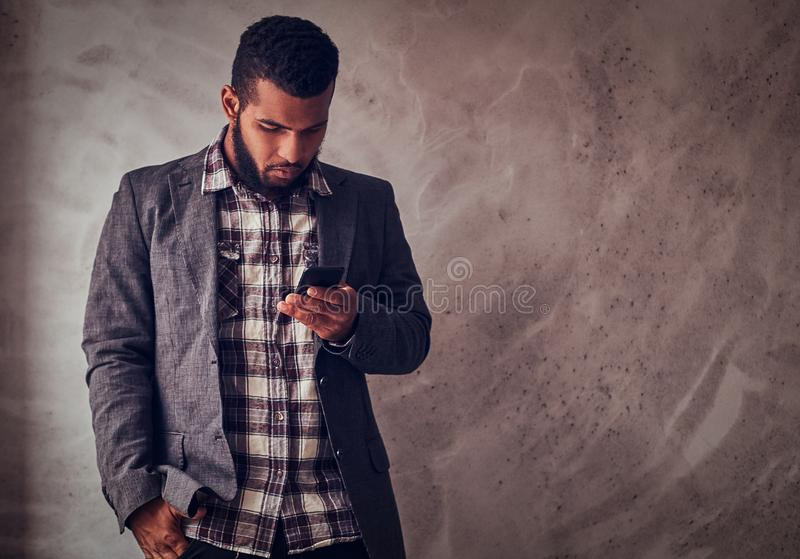 African-American guy using a phone in a studio. African-American guy using a phone while standing next to a textured gray wall in a studio stock images