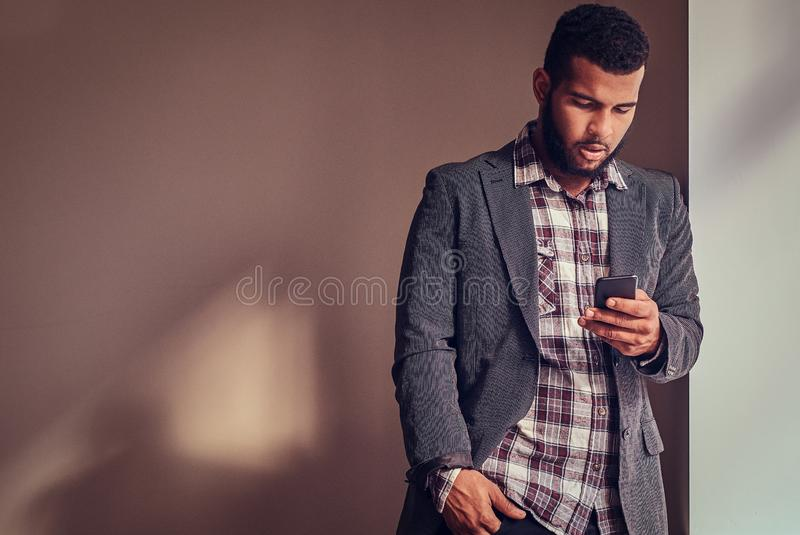 African-American guy using a phone in a studio. African-American guy using a phone while leaning on a wall in a studio stock images