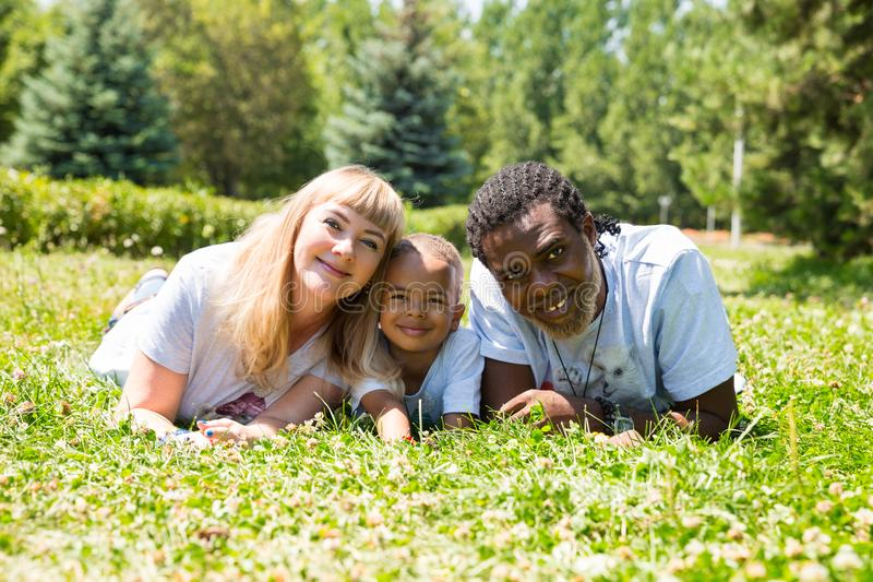 African American happy family: black father, mom and baby boy on nature. Use it for a child, parenting or love concept. African American happy family: black royalty free stock photography