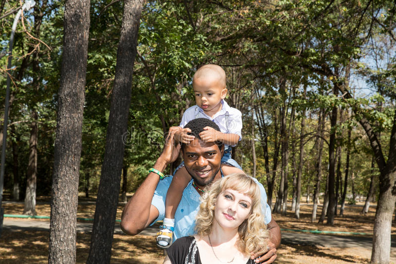 African American happy family: black father, mom and baby boy on nature. Use it for a child, parenting or love concept royalty free stock images