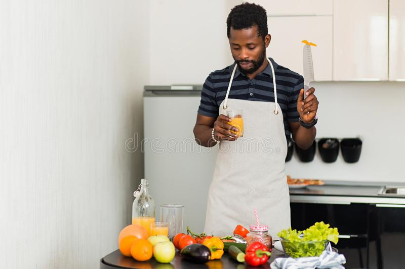 African man preparing healthy food at home in kitchen stock photos