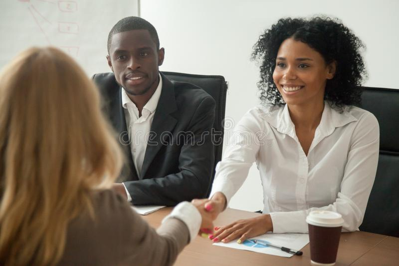 African american hr team welcoming female applicant at job inter. View, diverse businesswomen shaking hands at multi ethnic group meeting, handshaking and good stock image