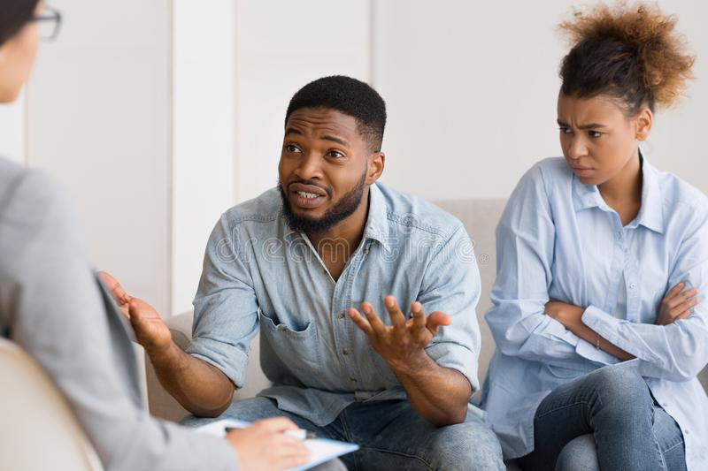 African American Husband Talking To Psychologist Sitting Next To Wife. Marriage Therapy Session. African American Husband Sitting Next To His Displeased Wife And royalty free stock photos