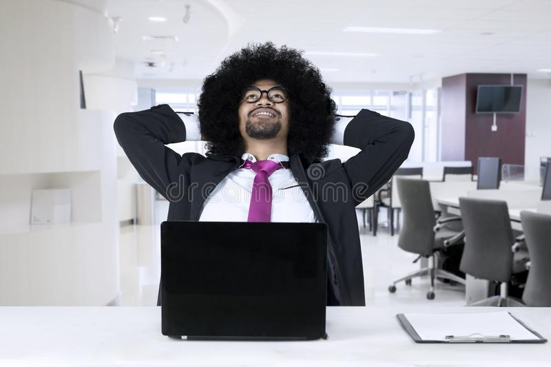 African american with laptop relaxing at office royalty free stock photography