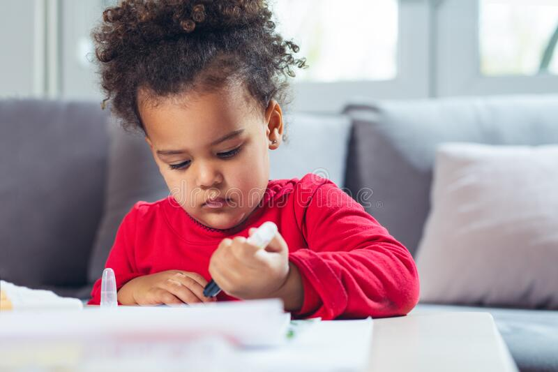 African American little girl drawing with colored pencils. royalty free stock images