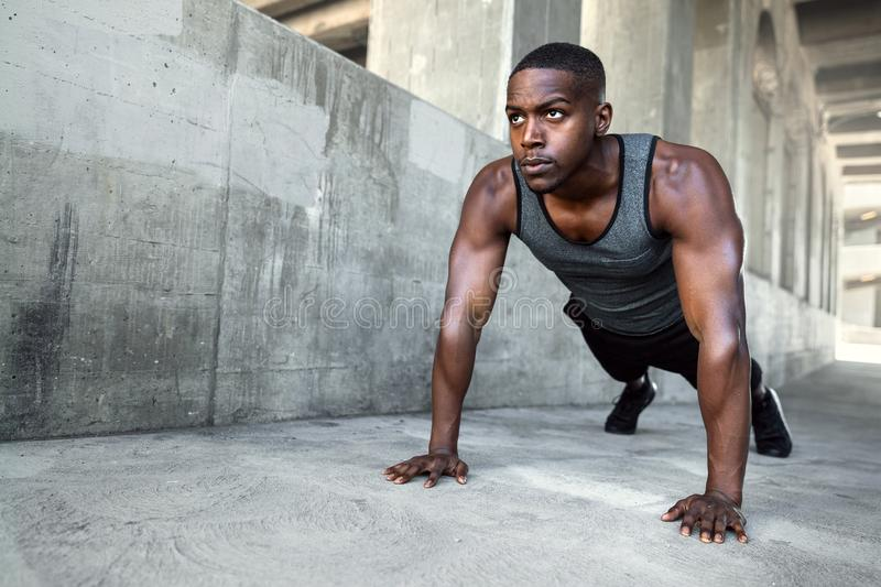African american male athlete, city urban training, fitness push ups on concrete with copy space. Determined african american male athlete training in city, on royalty free stock images