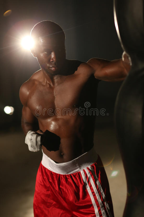 African American male boxer hitting punch bag in red shorts at the gym stock image