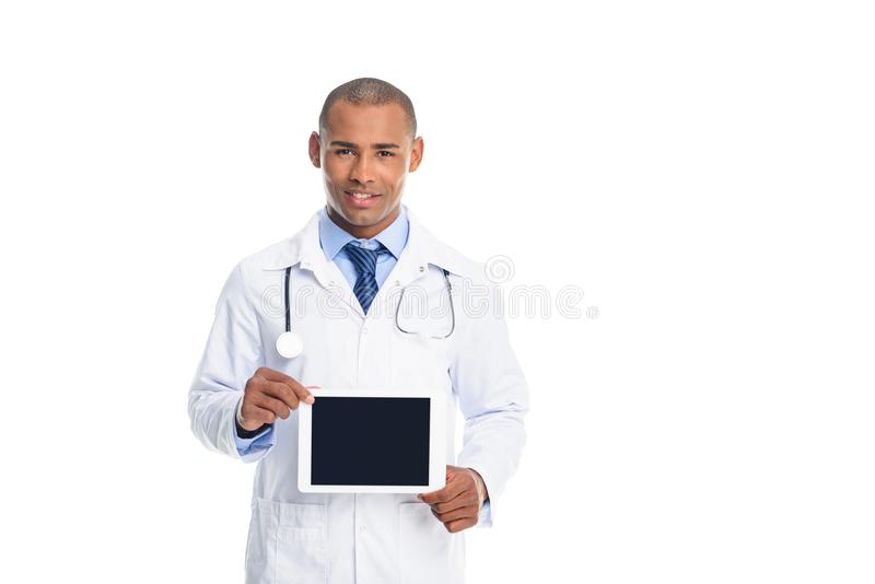 African american male doctor in white coat with tablet with blank screen,. Isolated on white royalty free stock images