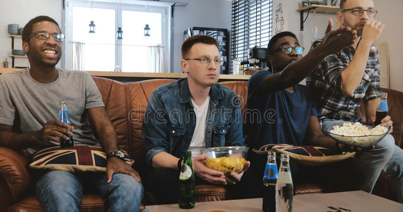 African American male friends watch sports on TV. Multi ethnic geeky fans concentrated and serious on couch with popcorn stock images
