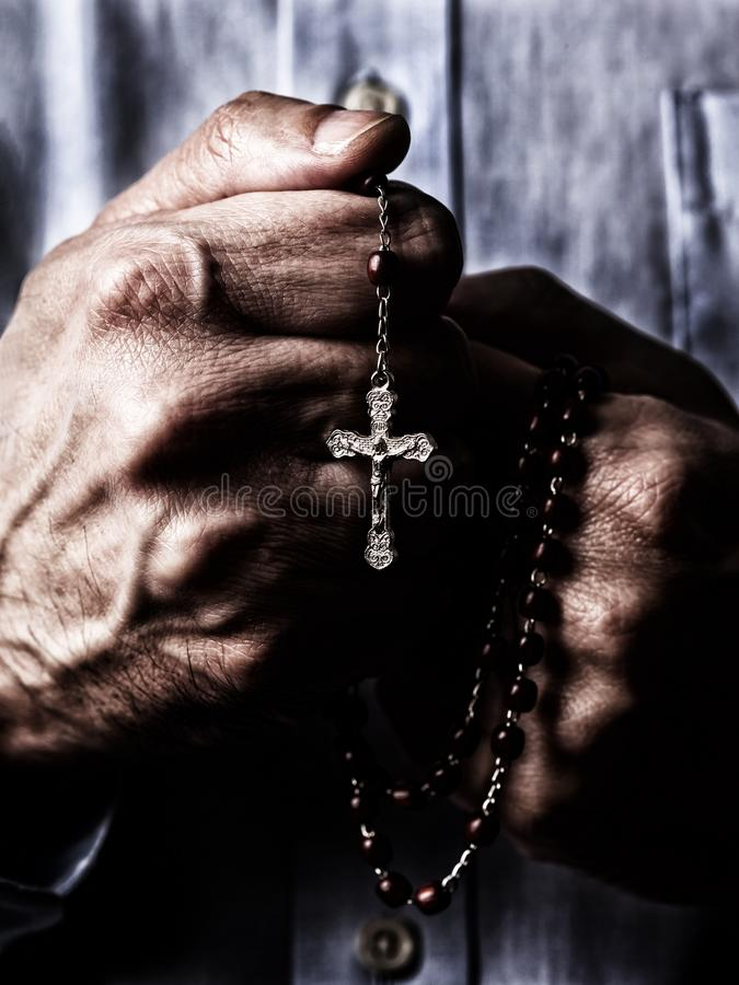 African American male hands praying holding a beads rosary with Jesus Christ in the cross or Crucifix on black background. Mature Afro American man with stock images