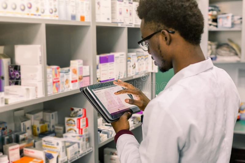 African American male pharmacist making notes on digital tablet in pharmacy, drug quality control stock images