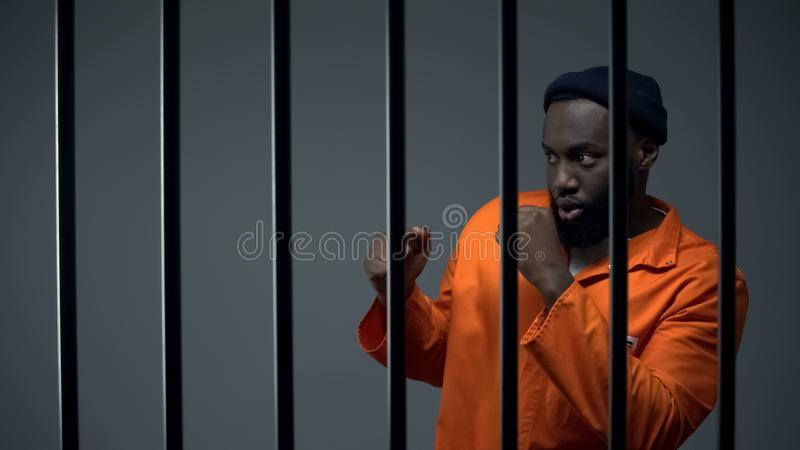 African-american male prisoner preparing to box in cell with inmate, quarrel stock photos