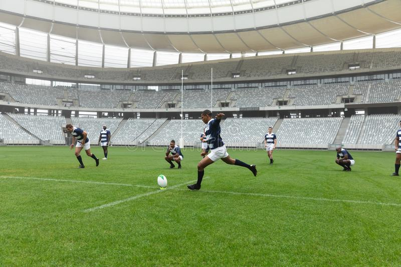African American male rugby player kicking rugby ball in stadium. Side view of  African American male rugby player kicking rugby ball in stadium. With players stock photo