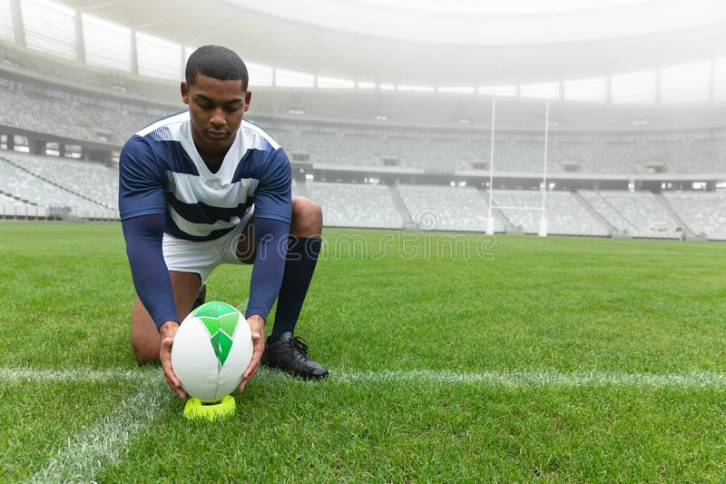 African American male rugby player placing rugby ball on the stand in stadium. Front view of African American male rugby player placing rugby ball on the stand royalty free stock images