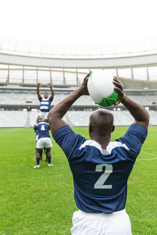 African American male rugby player throwing rugby ball in stadium. Rear view of African American male rugby player throwing rugby ball in stadium. With players royalty free stock photo